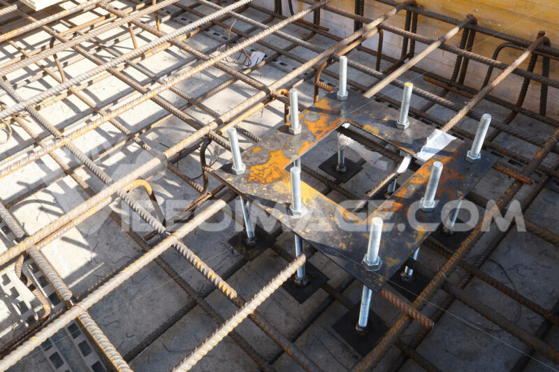 Construction site for a building with a steel structure. Plates with anchor bolts for mounting steel columns on a reinforced concrete foundation. - MyVideoimage.com
