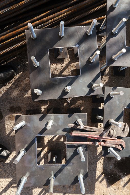 Construction site for a building with a steel structure. Plates with anchor bolts for mounting steel columns on a reinforced concrete foundation. - LEphotoart.com
