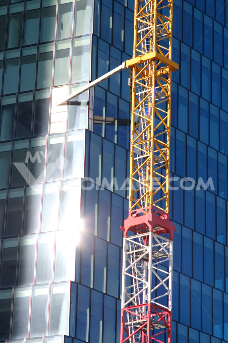 Construction site tower crane for the construction of the PWC Libeskind skyscraper in Milan. Glass facade with sun reflection. - MyVideoimage.com