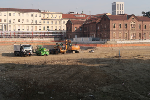 Construction site vehicles (trucks, excavators, bulldozers) in a large excavation for the construction of the new building of the Maggiore Policlinico hospital in Milan. - MyVideoimage.com