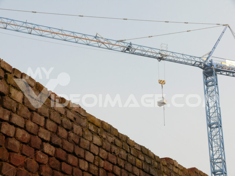 Construction site with cranes and a solid brick wall. - MyVideoimage.com