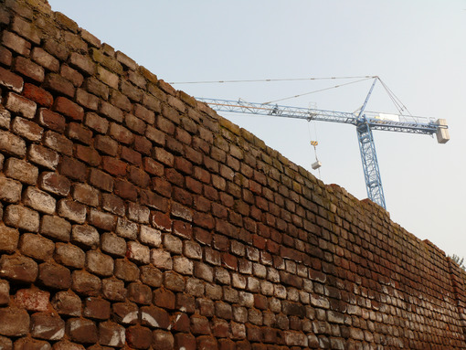 Construction site with cranes and a solid brick wall. Cantieri edili. - LEphotoart.com