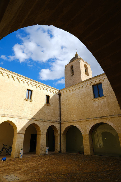 Convent of Sant'Agostino in Matera. Beige stone facade with blue sky and clouds. - LEphotoart.com