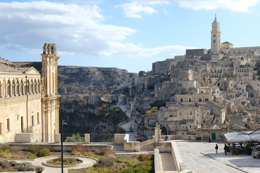 Convent of Sant'Agostino in Matera. Beige stone facade. In the background the city with the church and the bell tower. - MyVideoimage.com