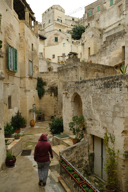 Courtyard in a street of the ancient city of Matera. A person walks down the street. Houses in tufa stone. - MyVideoimage.com