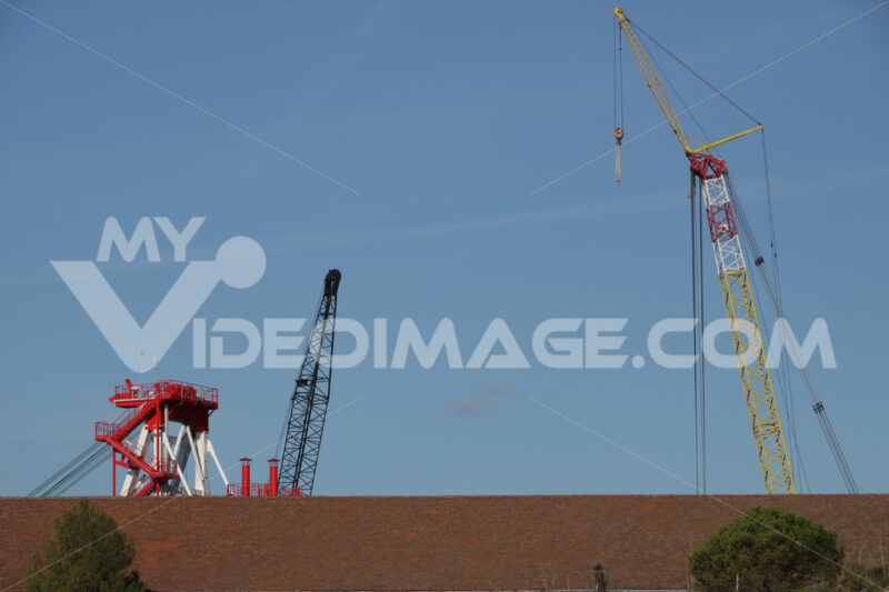 Cranes of a shipyard emerge from the roof of a building. - MyVideoimage.com