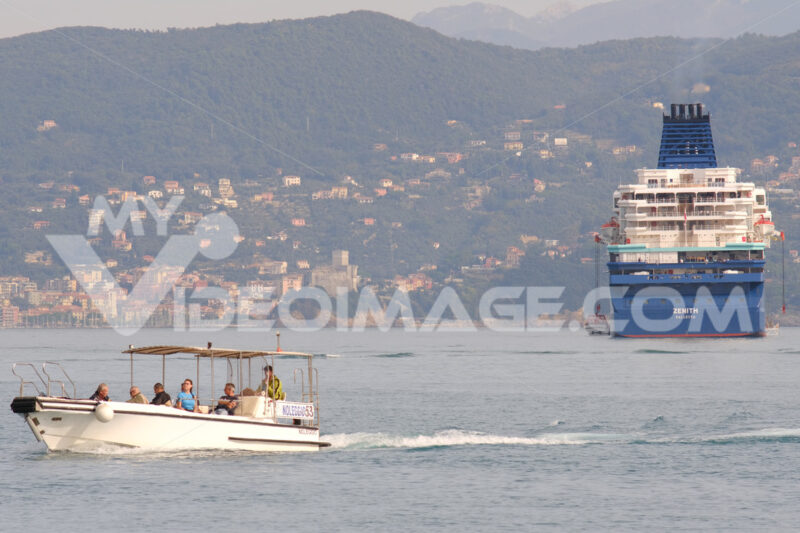 Cruise ship anchored in the Gulf of La Spezia opposite Portovenere. In the background, moving boats and the Apuan Alps. - MyVideoimage.com