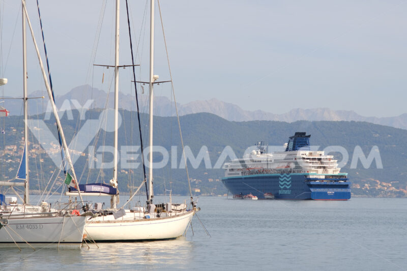 Cruise ship anchored in the Gulf of La Spezia opposite Portovenere. In the foreground sailboats moored at the port, near the Cinque Terre. Foto navi. Ships photo.