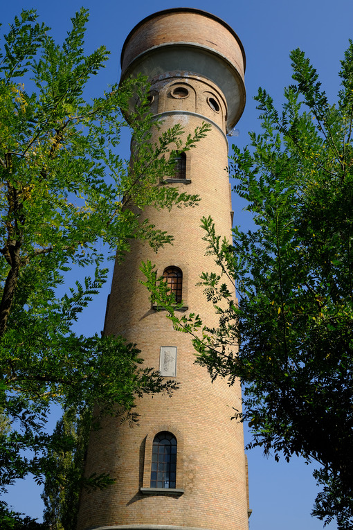 Cylindrical tower. Cylindrical brick tower soars into the blue sky. Stock photos. - MyVideoimage.com | Foto stock & Video footage