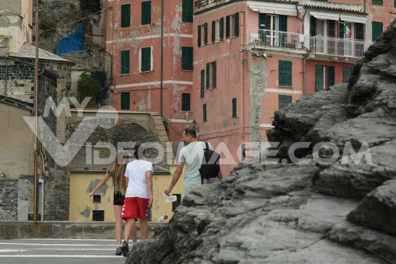 Dad with children walking among typical Ligurian houses in the town of Vernazza. In the foreground the cliff overlooking the sea. Royalty free stock photography. Città italiane. Italian cities.