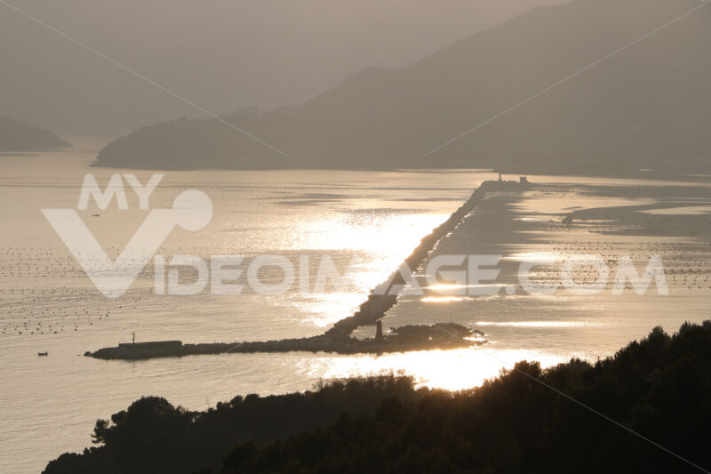 Dam of the port of La Spezia that separates the gulf from the open sea. Reflections on the sea at sunset. - MyVideoimage.com