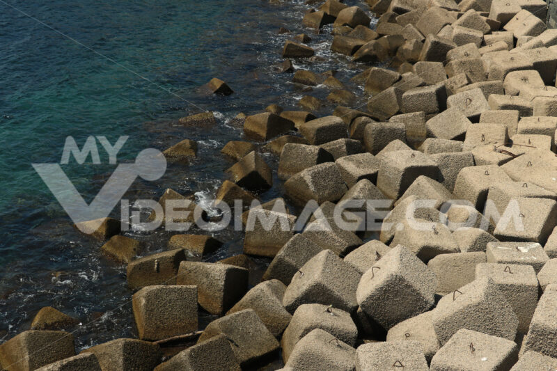 Dam on the sea with concrete blocks. An artificial reef for the protection of the coast in Forio d'Ischia near Naples. - MyVideoimage.com