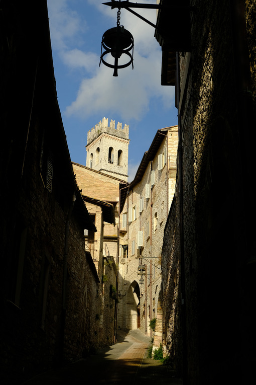 Deserted road in Assisi, Italy. Alley of the city of Assisi with bell tower and stone houses. Narrow street of the city with the walls of the stone houses. Deserted road. - MyVideoimage.com | Foto stock & Video footage