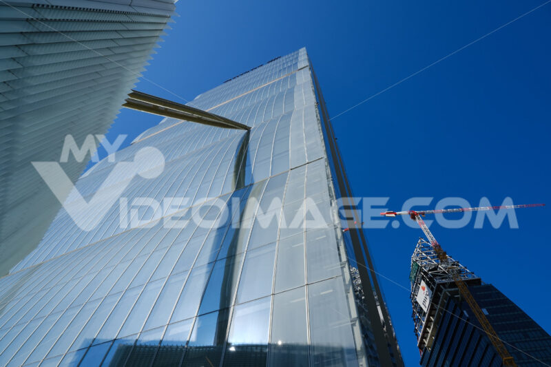 Detail of the facade of the Allianz skyscraper by Arata Isozaki. in Milan. Complex of the three towers at Citylife. In the background  Libeskind towe under construction. - MyVideoimage.com