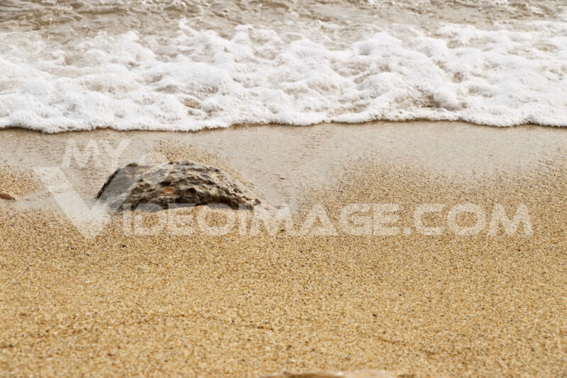 Detail of yellow ocher beach with sea wave. The water is fringed on a semi-stone submerged in the sand. - MyVideoimage.com