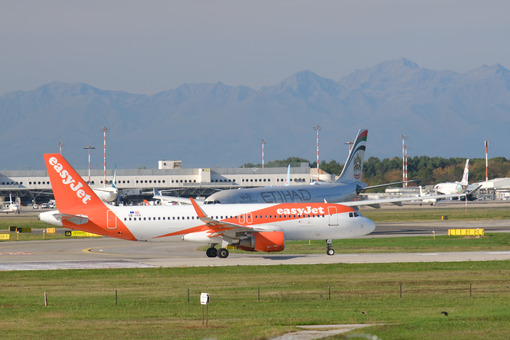 Easyjet Airbus airplane maneuvering on the Malpensa airport runway. In the background the buildings and Etihad planes. - MyVideoimage.com