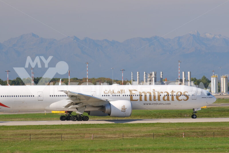 Emirates Boeing 777-300ER  airplane on the Malpensa airport runway.  In the background the mountains of the Alps. - MyVideoimage.com