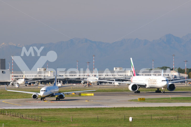 Emirates Boeing 777-31H  airplane on the Malpensa airport runway. 	In the background the terminal 1. - MyVideoimage.com