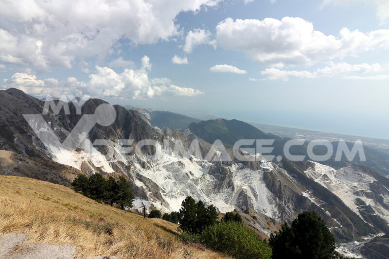Escavazione marmo alle cave. Panorama of the white marble quarries of Carrara on the Apuan Alps. The white parts of the mountain highlight the areas of stone extraction. - MyVideoimage.com | Foto stock & Video footage