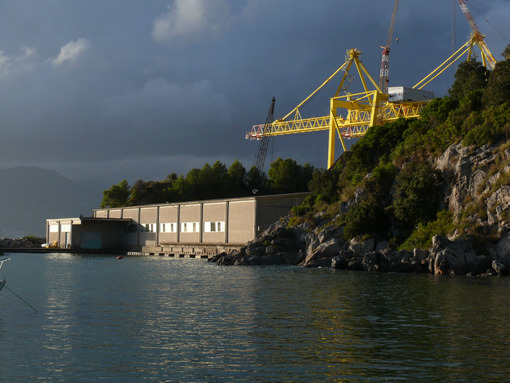 Establishment for the selection and packaging of mussels in La Spezia. In the background a large yellow crane of a shipyard. Photo at sunset with cloudy sky. - MyVideoimage.com