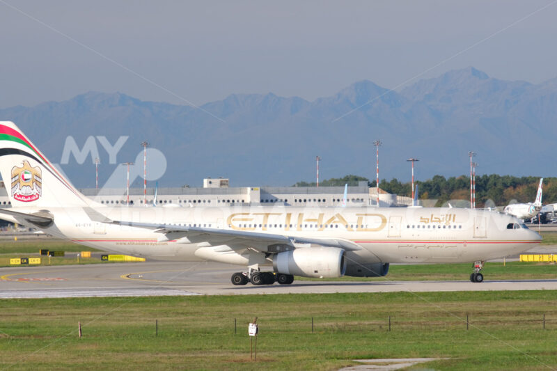 Etihad Airbus A330-243 airplane maneuvering on the Malpensa airport runway. In the background the buildings of Terminal 1 and parked airplanes. - MyVideoimage.com