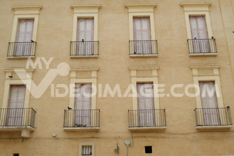 Facade of a Mediterranean palace with windows and balconies. Beige color plaster. - MyVideoimage.com