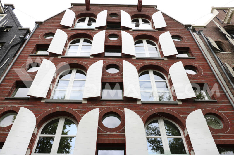 Facade of a brick house with white windows and shutters. - MyVideoimage.com