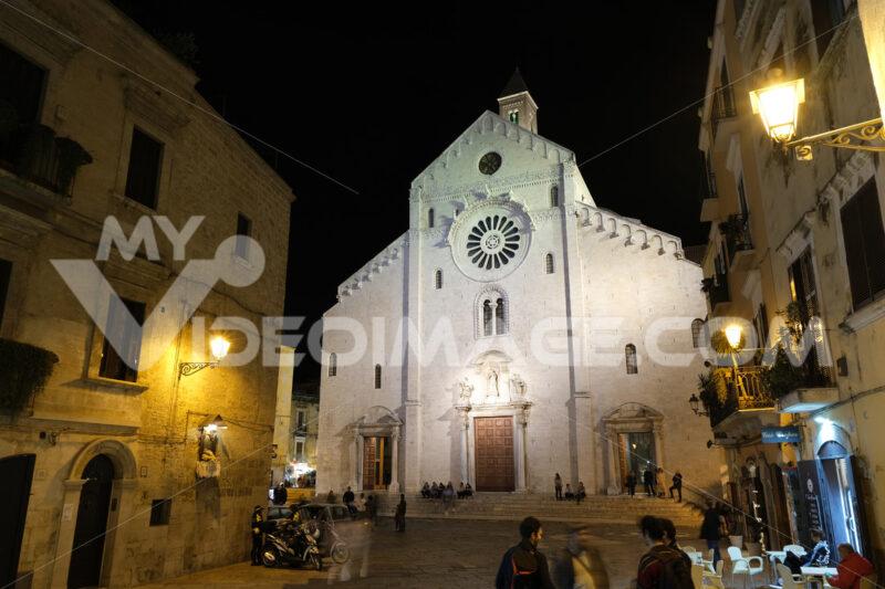 Facade of the Cathedral of San Sabino in Bari in limestone. Night shot with people walking. Foto Bari photo.