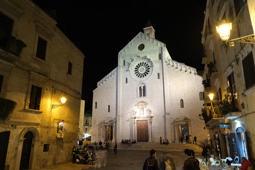Facade of the Cathedral of San Sabino in Bari in limestone. Night shot with people walking. Foto Bari photo.