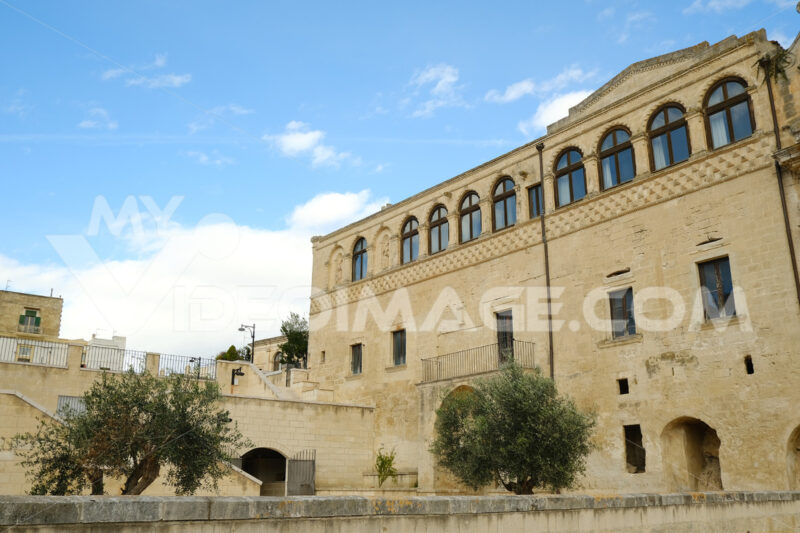 Facade of the Convent of Sant'Agostino in Matera. Courtyard with olive trees with leaves moving in the wind. - MyVideoimage.com | Foto stock & Video footage