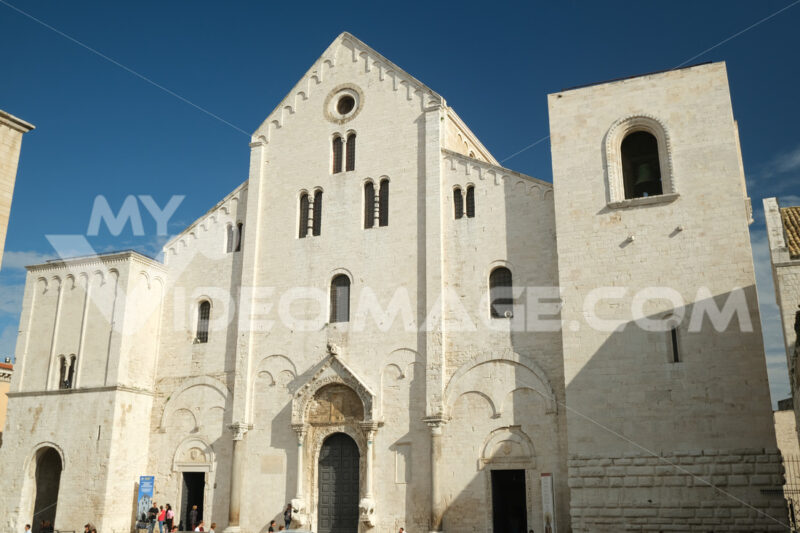 Façade of the church of San Nicola in Bari in limestone. Church with light stone walls with the blue sky background with clouds. Foto Bari photo.