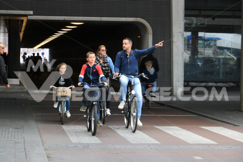Family cycling to Amsterdam central station. Child, mom and dad - MyVideoimage.com