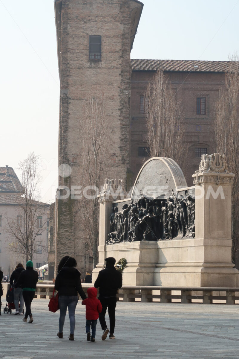Family with child and people walking in piazza della Pace in parma. In the background the monument to Giuseppe Verdi and the Palazzo della Pilotta. - MyVideoimage.com