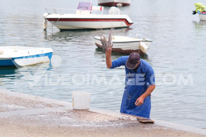 Fisherman at the port of Bari beats an octopus. At the market near the port the fishermen sell the fish caught. - MyVideoimage.com