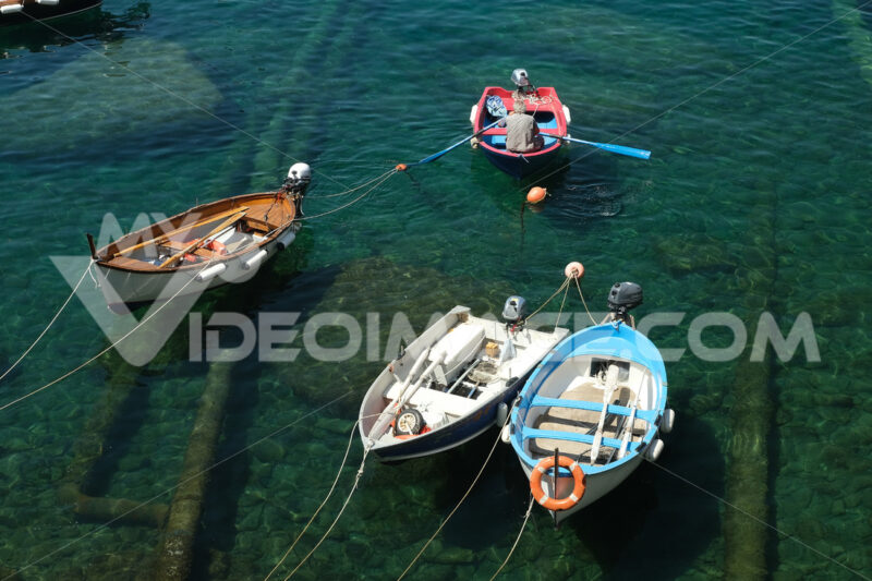 Fisherman with colorful rowboat in the blue sea of Liguria. Riomaggiore, Cinque Terre. - MyVideoimage.com