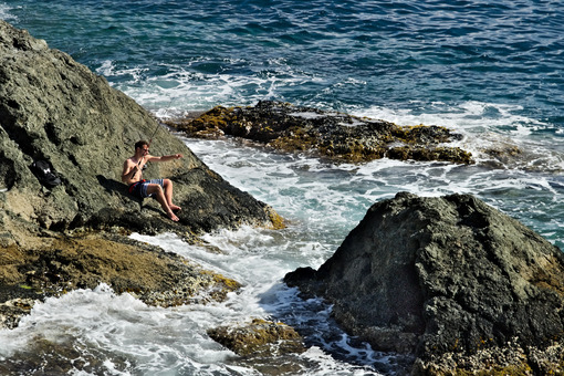 Fisherman with fishing rod on a rock on the sea near the Cinque - MyVideimage.com