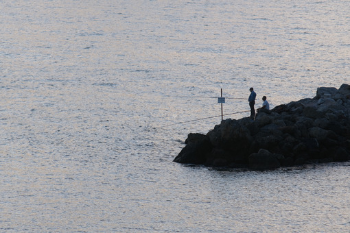 Fishermen with fishing rod on the rocks in La Spezia. Fishing from the shore is a sport widely practiced in Liguria. - MyVideoimage.com
