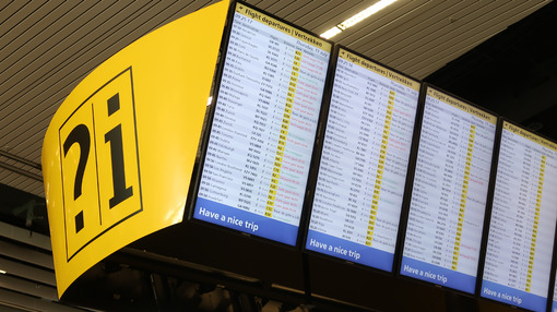 Flight info board at Amsterdam Schiphol airport. Help desk with - MyVideoimage.com