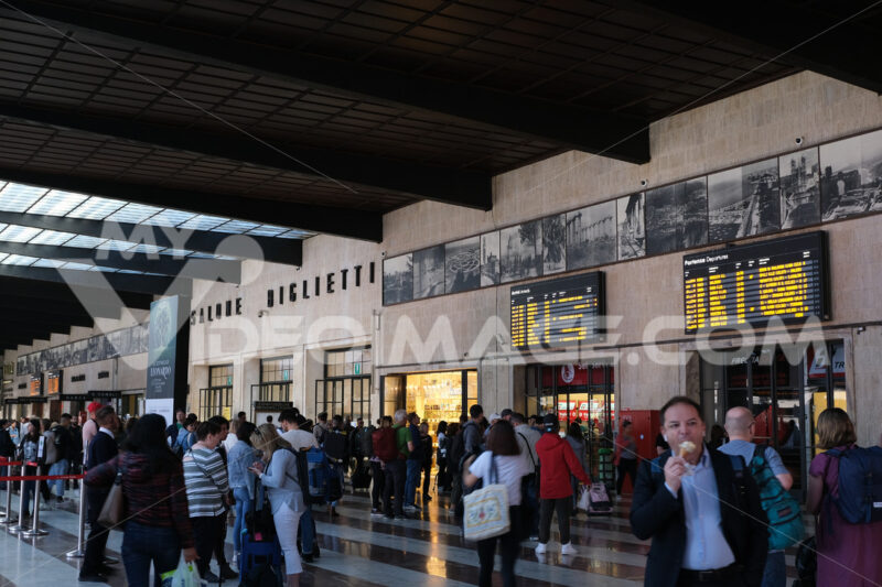 Florence train station with people walking. Scoreboards for arriving and departing trains. Project of the Tuscan Group with the Architect Giovanni Michelucci. - MyVideoimage.com