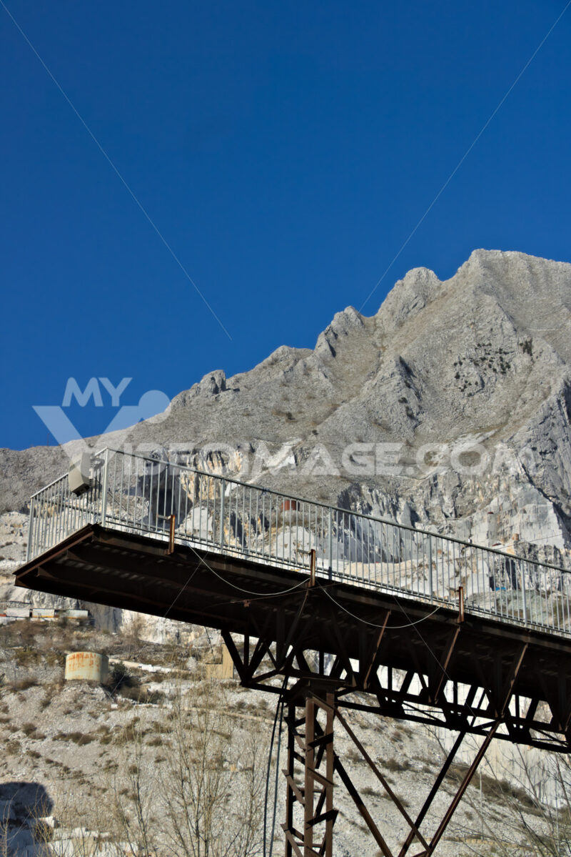 Footbridge. Apuan Alps, Carrara, Tuscany, Italy. March 28, 2019. Steel structure of a walkway with the backdrop of Monte Sagro - MyVideoimage.com | Foto stock & Video footage