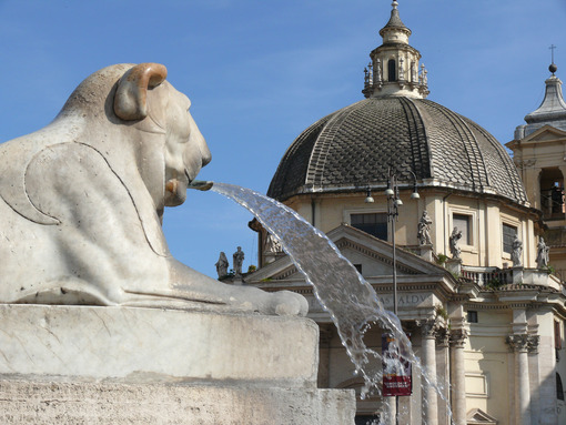 Fountain with a white marble lion statue in Piazza del Popolo in Rome. In the background the dome of one of the two twin churches. - MyVideoimage.com