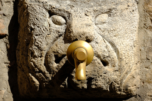 Fountain with brass faucet applied on an ancient mask carved on stone. - MyVideoimage.com