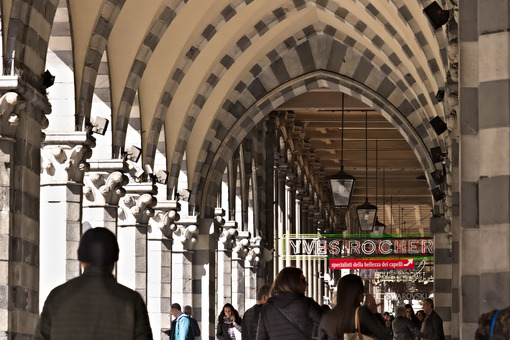 Genoa. People walk under an ancient arcade - MyVideoimage.com | Foto stock & Video footage