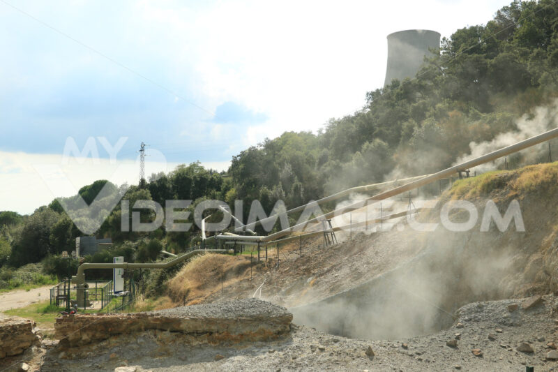 Geothermal field with fumaroles and steam pipes. Geothermal power station.Condensation towers in reinforced concrete. Larderello, Tuscany - MyVideoimage.com