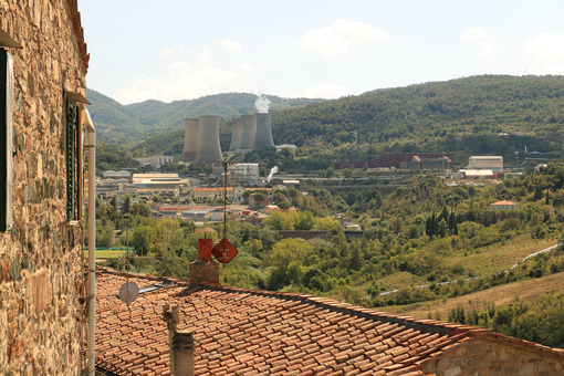 Geothermal power plant for electricity production. Condensation towers in reinforced concrete. A ancient stone farmhouse. Larderello, Tuscany, - MyVideoimage.com