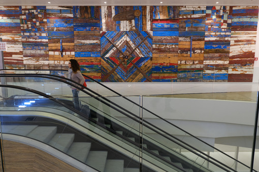 Girl on an escalator at Bari airport. Decorative panel with wooden slats made from old boats. - MyVideoimage.com
