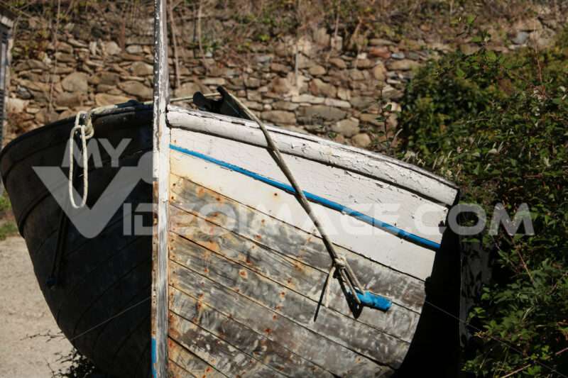 Gozzo, a typical wooden boat from Liguria pulled ashore in a square in the Cinque Terre. - LEphotoart.com
