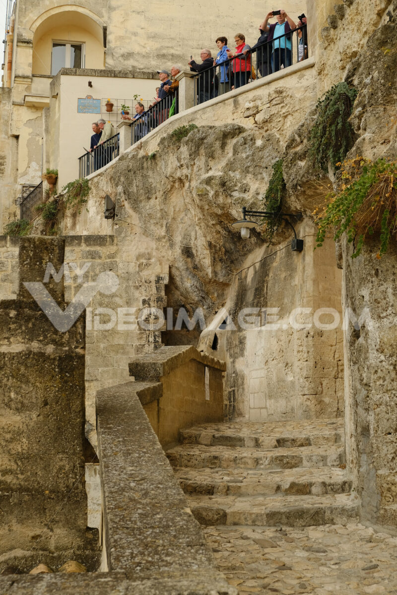 Group of tourists photographing the view from a terrace in the city of Matera. Street with beige-colored tuff stone wall. - MyVideoimage.com
