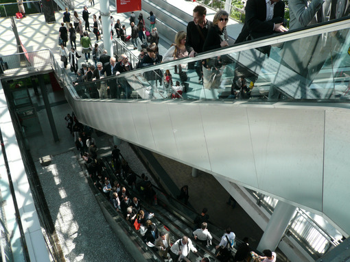 Groups of business people at the Milan fair. Escalators and moving belts. Modern architecture in glass and steel. - MyVideoimage.com