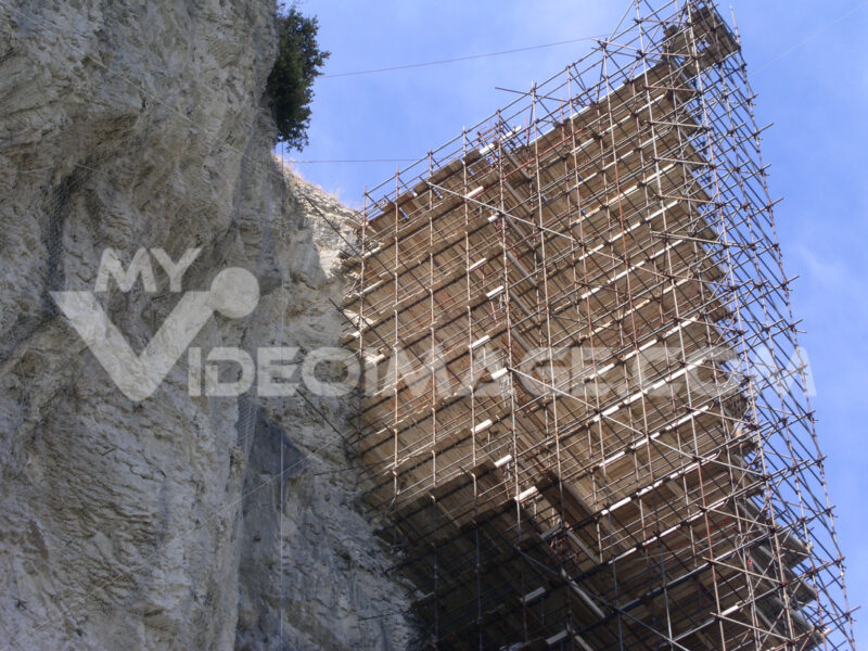 High metal scaffolding mounted on a rock spur. Blue sky background. Cantieri edili. - LEphotoart.com